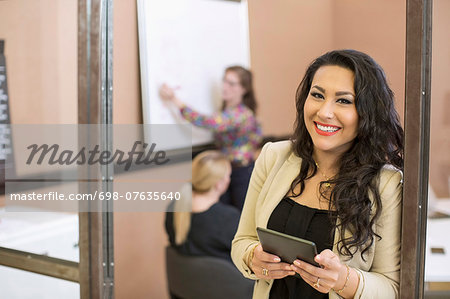 Portrait of happy businesswoman with digital tablet standing at board room entrance in office Stock Photo - Premium Royalty-Free, Image code: 698-07635640