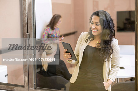 Happy businesswoman using digital tablet in creative office Stock Photo - Premium Royalty-Free, Image code: 698-07635641