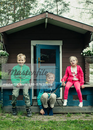 Portrait of siblings sitting on porch Stock Photo - Premium Royalty-Free, Image code: 698-07635678