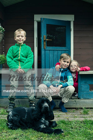 Portrait of siblings with dog sitting on porch Stock Photo - Premium Royalty-Free, Image code: 698-07635679