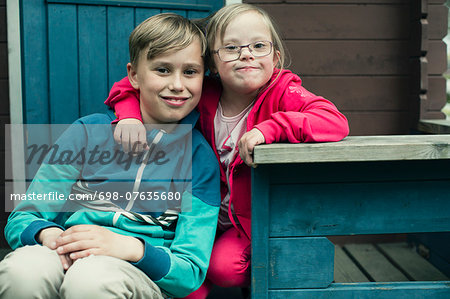 Portrait of handicapped girl with arm around brother sitting on porch Stock Photo - Premium Royalty-Free, Image code: 698-07635680