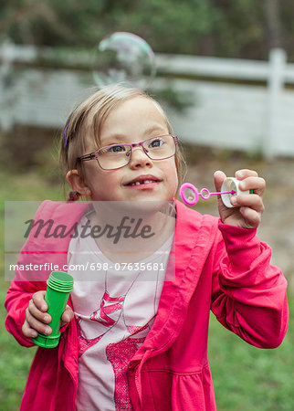 Girl playing with bubble wand in lawn Stock Photo - Premium Royalty-Free, Image code: 698-07635681