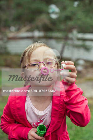 Girl blowing bubbles in lawn Stock Photo - Premium Royalty-Free, Image code: 698-07635682