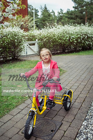Portrait of girl with down syndrome riding bicycle in lawn Stock Photo - Premium Royalty-Free, Image code: 698-07635683