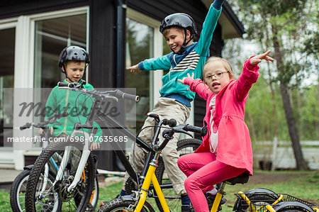 Portrait of girl with arms outstretched riding bicycle with brothers in lawn Stock Photo - Premium Royalty-Free, Image code: 698-07635685