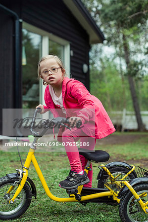 Portrait of girl with down syndrome riding bicycle in lawn Stock Photo - Premium Royalty-Free, Image code: 698-07635686