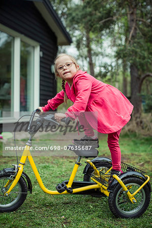 Portrait of girl with down syndrome balancing on bicycle in lawn Stock Photo - Premium Royalty-Free, Image code: 698-07635687