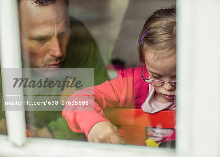View of father and daughter looking down through window Stock Photo - Premium Royalty-Free, Image code: 698-07635688