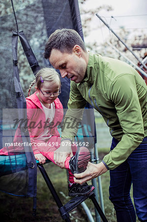 Father assisting handicapped daughter in wearing shoes at lawn Stock Photo - Premium Royalty-Free, Image code: 698-07635692