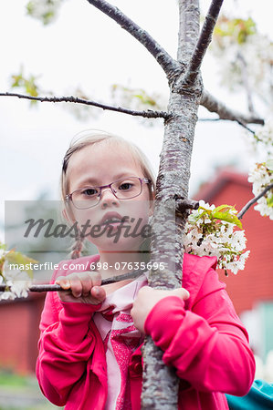 Portrait of girl with down syndrome holding tree branch in yard Stock Photo - Premium Royalty-Free, Image code: 698-07635695