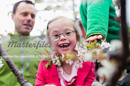 Portrait of happy handicapped girl with father and brother in yard Stock Photo - Premium Royalty-Free, Image code: 698-07635697