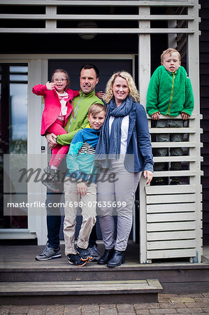Portrait of happy family standing at porch Stock Photo - Premium Royalty-Free, Image code: 698-07635699