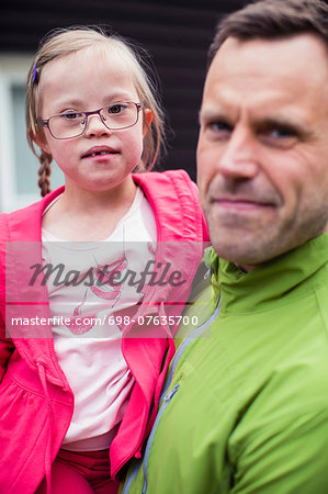 Portrait of girl with down syndrome carried by father Stock Photo - Premium Royalty-Free, Image code: 698-07635700