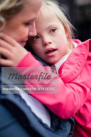 Girl with down syndrome carried by mother Stock Photo - Premium Royalty-Free, Image code: 698-07635701