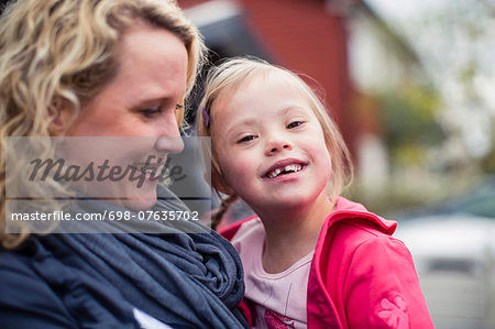 Portrait of happy girl with down syndrome carried by mother Stock Photo - Premium Royalty-Free, Image code: 698-07635702