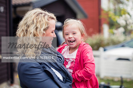 Portrait of girl with mother laughing in yard Stock Photo - Premium Royalty-Free, Image code: 698-07635703
