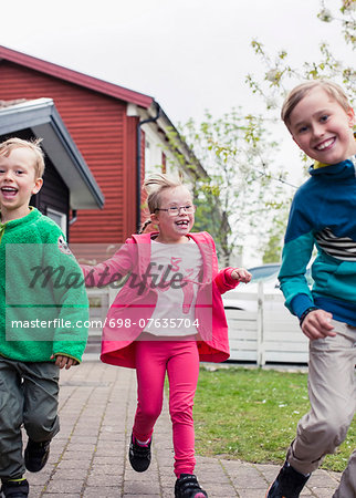 Girl with brothers running in lawn Stock Photo - Premium Royalty-Free, Image code: 698-07635704