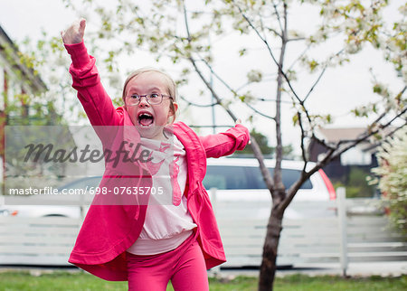 Excited girl with arms outstretched enjoying in lawn Stock Photo - Premium Royalty-Free, Image code: 698-07635705