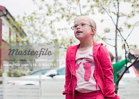 Thoughtful girl with down syndrome looking away while standing in lawn Stock Photo - Premium Royalty-Free, Image code: 698-07635706