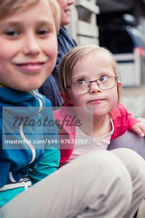 Girl with down syndrome looking at brother outdoors Stock Photo - Premium Royalty-Free, Image code: 698-07635707