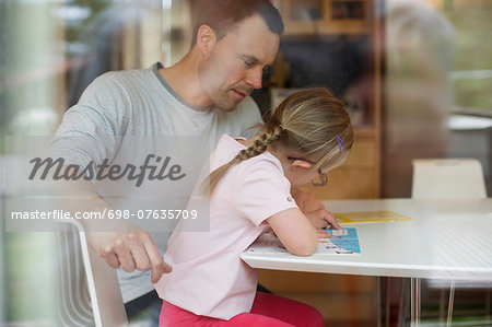 Father assisting handicapped girl in studies at table Stock Photo - Premium Royalty-Free, Image code: 698-07635709