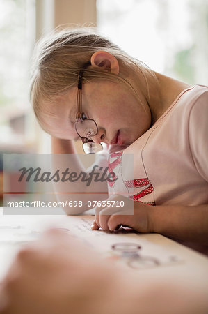 Girl with down syndrome studying at table Stock Photo - Premium Royalty-Free, Image code: 698-07635710