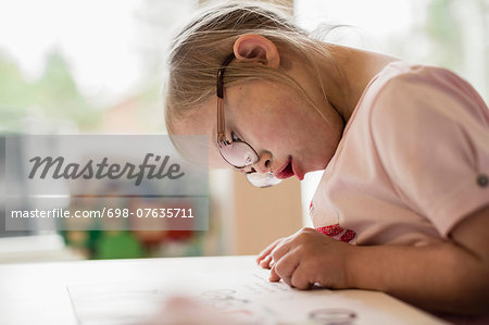 Girl with down syndrome studying at table Stock Photo - Premium Royalty-Free, Image code: 698-07635711