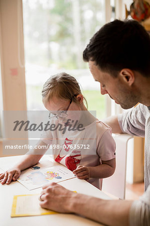 Father assisting handicapped girl in studying at home Stock Photo - Premium Royalty-Free, Image code: 698-07635712