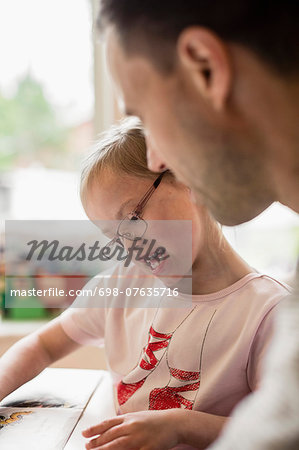 Girl with down syndrome studying by father at home Stock Photo - Premium Royalty-Free, Image code: 698-07635716