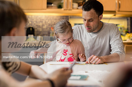 Father teaching daughter with son in foreground at home Stock Photo - Premium Royalty-Free, Image code: 698-07635718
