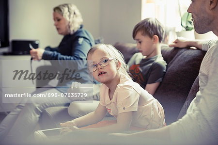 Portrait of handicapped girl sitting with family on sofa at home Stock Photo - Premium Royalty-Free, Image code: 698-07635729