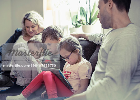 Family of five sitting on sofa at home Stock Photo - Premium Royalty-Free, Image code: 698-07635730