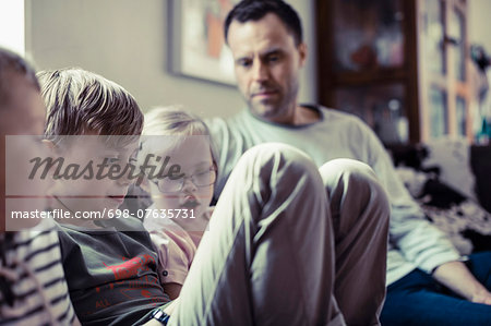 Siblings sitting with father in house Stock Photo - Premium Royalty-Free, Image code: 698-07635731
