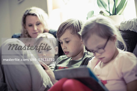 Siblings sitting with mother in house Stock Photo - Premium Royalty-Free, Image code: 698-07635732