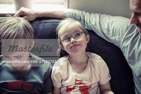 Girl with down syndrome looking at father by brother on sofa Stock Photo - Premium Royalty-Free, Image code: 698-07635733