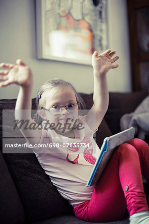 Portrait of handicapped girl with digital tablet raising arms on sofa Stock Photo - Premium Royalty-Free, Image code: 698-07635734