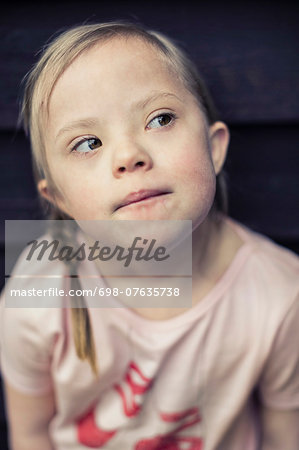 Thoughtful girl with down syndrome looking away Stock Photo - Premium Royalty-Free, Image code: 698-07635738
