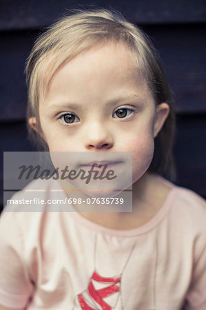 Thoughtful girl with down syndrome looking away Stock Photo - Premium Royalty-Free, Image code: 698-07635739