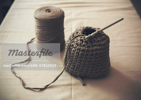 Half-finished woolen purse with spool on table Stock Photo - Premium Royalty-Free, Image code: 698-07812929