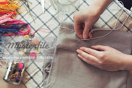 High angle view of woman stitching fabric on table at home Stock Photo - Premium Royalty-Free, Image code: 698-07812936