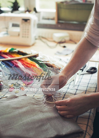 Cropped image of woman stitching fabric on table at home Stock Photo - Premium Royalty-Free, Image code: 698-07812938