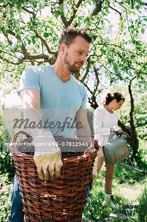 Man carrying wicker basket with woman gardening in background at yard Stock Photo - Premium Royalty-Free, Image code: 698-07812946