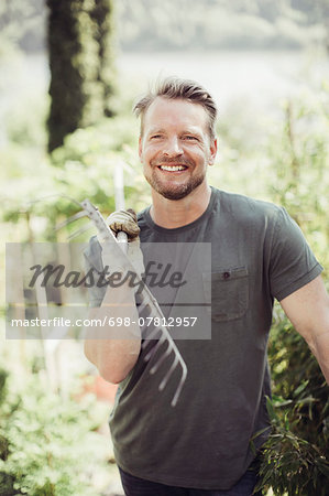 Happy man looking away while carrying gardening fork on shoulder at yard Stock Photo - Premium Royalty-Free, Image code: 698-07812957