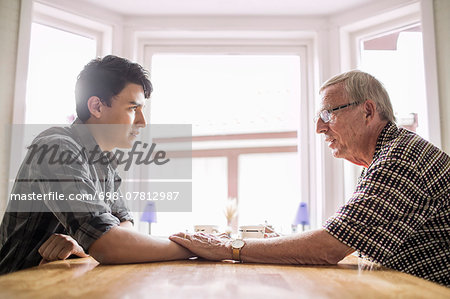 Side view of grandfather consoling grandson at table Stock Photo - Premium Royalty-Free, Image code: 698-07812987