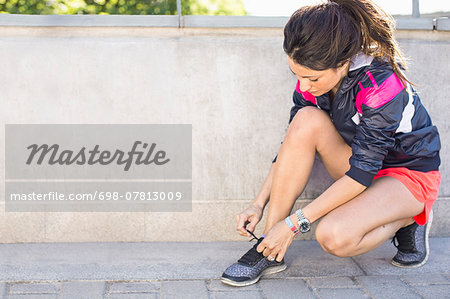 Full length of fit woman tying shoelace before jogging on bridge Stock Photo - Premium Royalty-Free, Image code: 698-07813009