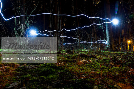 Blue light trails in forest Stock Photo - Premium Royalty-Free, Image code: 698-07813042