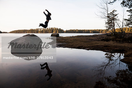 Full length of boy jumping off stone over water Stock Photo - Premium Royalty-Free, Image code: 698-07813043