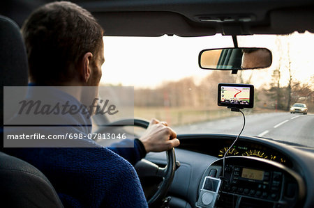 Rear view of man driving car while using GPS Stock Photo - Premium Royalty-Free, Image code: 698-07813046