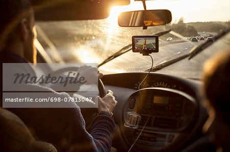 Cropped image of man driving car while using GPS by daughter Stock Photo - Premium Royalty-Free, Image code: 698-07813047