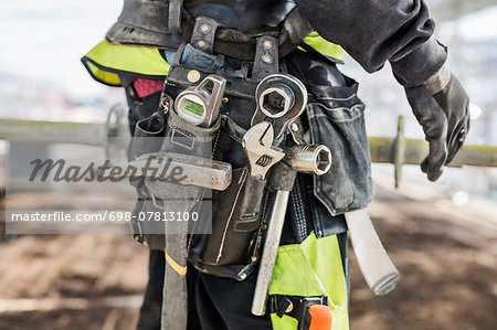 Midsection of construction worker wearing tool belt at site Stock Photo - Premium Royalty-Free, Image code: 698-07813100